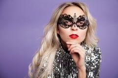 Sexig blond flicka i en spets- maskering På en lila bakgrund utrymme för text arkivbilder