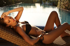 Sexig blond flicka i svart bikini som kopplar av bredvid en simbassäng Arkivfoton