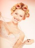 Sexig blond flicka med hårrullar i underkläder och pärlor som har gyckel Arkivbild