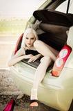 Sexig blond flicka som ligger i stam av bilen Arkivfoto