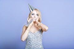 Sexig blond klänning för silver för partiflicka bärande och blåsa partivisslingen Arkivbilder
