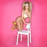 Sexig blond kvinna i bikinin som knäfaller på stol Arkivfoto