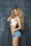 Sexig blond kvinna i den vita underkläderna på en mörk vägg Royaltyfria Bilder