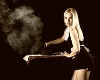 Sexig blond kvinna i hushållerskadräkten som stryker den vita skjortan med gammalt järn retro stil på en mörk bakgrund royaltyfria foton