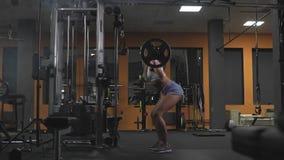 Sexig blond kvinna i idrottshallen som gör övningar på satt med skivstången i ultrarapid stock video