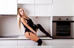 Sexig blond kvinna i kök Royaltyfria Bilder