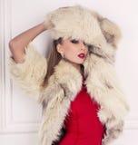 sexig blond kvinna i röd klänning med pälslaget Royaltyfri Bild