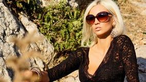Sexig blond kvinna i svart klänning med solglasögon Royaltyfria Bilder
