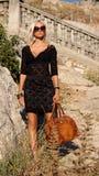 Sexig blond kvinna i svart klänning med solglasögon Fotografering för Bildbyråer