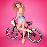 Sexig blond kvinna med en cykel Fotografering för Bildbyråer
