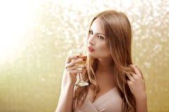 Sexig blond kvinna med ett exponeringsglas av champagne på partiet Arkivfoto
