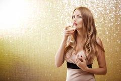 Sexig blond kvinna med ett exponeringsglas av champagne på partiet Arkivbild