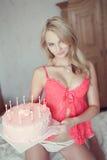 Sexig blond kvinna med födelsedagkakan på säng Royaltyfri Foto