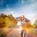 Sexig blond kvinna som går på landsvägen Fotografering för Bildbyråer