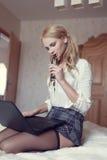 Sexig blond kvinna som knäfaller med bärbara datorn Royaltyfri Foto