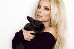 Sexig blond kvinnlig modell som står på en vit bakgrund arkivfoto