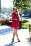 Sexig blond modell som poserar på thgatan i röd sommarklänning royaltyfri bild
