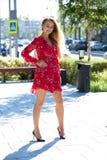 Sexig blond modell som poserar på thgatan i röd sommarklänning royaltyfria foton