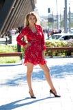 Sexig blond modell som poserar på thgatan i röd sommarklänning royaltyfria bilder