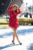 Sexig blond modell som poserar på thgatan i röd sommarklänning arkivfoto