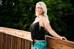 Sexig blond modemodell på en bro Arkivfoto