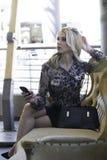 Sexig blond stads- kvinnainnehavtelefon Arkivfoto