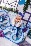 Sexig blondin i blå julhatt av Santa Claus sammanträde på en Ch Arkivbilder