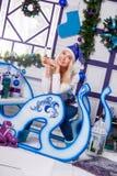 Sexig blondin i blå julhatt av Santa Claus sammanträde på en Ch Arkivbild