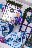 Sexig blondin i blå julhatt av Santa Claus sammanträde på en Ch Fotografering för Bildbyråer