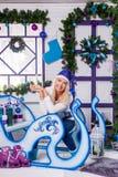 Sexig blondin i blå julhatt av Santa Claus sammanträde på en Ch Arkivfoto