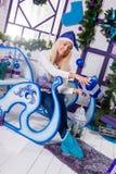 Sexig blondin i blå julhatt av Santa Claus sammanträde på en Ch Royaltyfri Bild