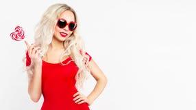 Sexig blondin i rött Sinnlig ung kvinna med lollypop Romantiskt begrepp Erotiskt begrepp arkivfoton