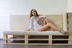 Sexig blondin i skjortan som poserar på soffan
