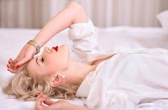 Sexig blondin med röd läppstift, i den vita manliga skjortan som ligger på vit säng i profil royaltyfria bilder