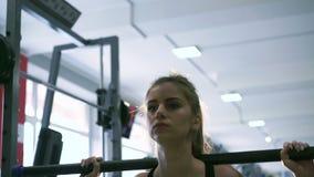 Sexig blondin som utför squats i idrottshallen 4K arkivfilmer
