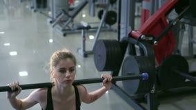 Sexig blondin som utför squats i idrottshallen 4K lager videofilmer