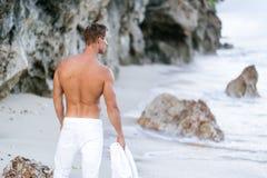 Sexig brunbr?nd man f?r baksikt i vita fl?sanden som g?r p? stranden med havv?gor p? bakgrund arkivfoto