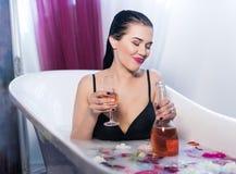 Sexig brunett drucken kvinna som kopplar av i ett varmt bad Royaltyfri Foto