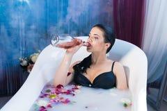 Sexig brunett drucken kvinna som kopplar av i ett varmt bad Arkivbild