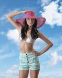 Sexig brunett med kortslutningar och hatten Arkivbild