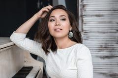 Sexig brunett med mycket långt hårsammanträde på pianot Arkivfoton