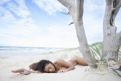 Sexig brunett som sover i sanden Arkivfoton