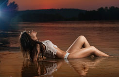 Sexig brunettkvinna i damunderkläder som lägger i flodvatten Ungt kvinnligt koppla av på stranden under solnedgång Göra perfekt k Arkivbilder