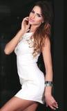 Sexig brunettkvinna i den vita klänningen. Arkivfoto