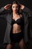 Sexig brunettkvinna med retro svart damunderkläder Royaltyfri Foto