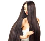 Sexig brunettmodellflicka som trycker på hennes långa skinande hår arkivfoton