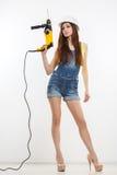 Sexig byggmästarekvinna med en drillborr i henne händer Royaltyfri Foto