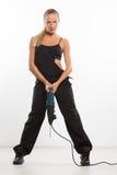 Sexig byggmästarekvinna med en drillborr i henne händer Royaltyfri Bild
