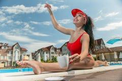 Sexig dam vid pölen i en röd baddräkt med en kopp kaffe solbada f?r p?l royaltyfri bild