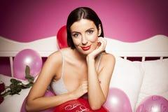 Sexig damunderkläderkvinna på sängen med valentindaggarneringar Royaltyfri Bild